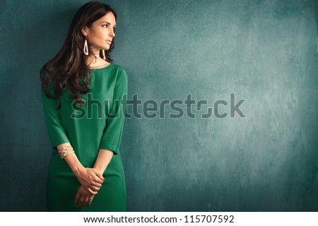 elegant mature woman in green dress lean on wall - stock photo