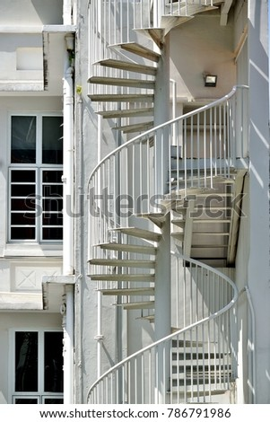 elegant metal spiral staircase on the side of a shop house in chinatown singapore