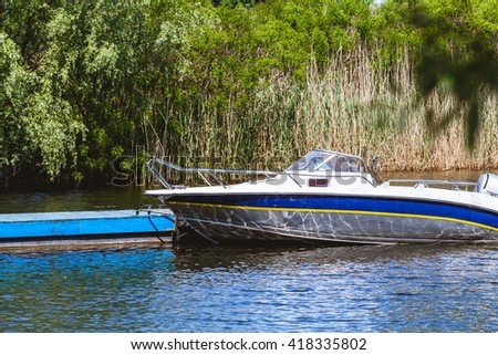 Elegant modern motor boat is at the dock in the bay river summer day  - stock photo