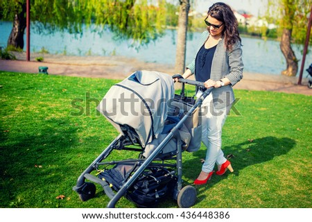 elegant mother smiling with baby in park. Mother walking child with pram or baby stroller - stock photo