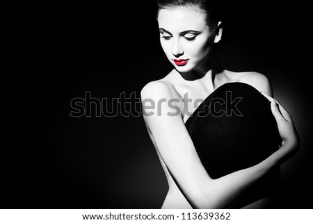 Elegant naked young woman posing with black pot hat. Light and shadow. - stock photo