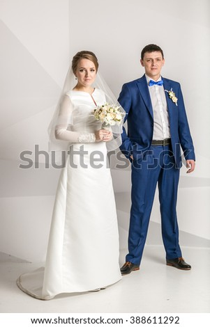 Elegant newly married couple posing in studio over white background - stock photo