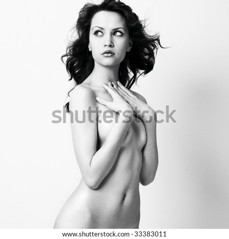 Elegant nude woman with curly hair. Studio portrait.
