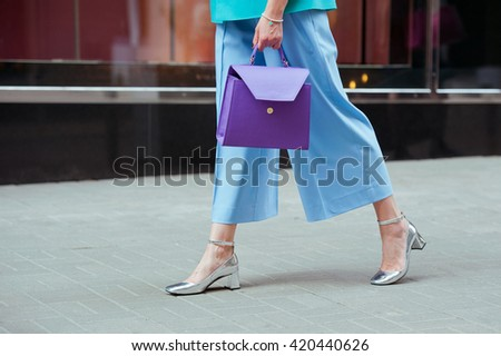 Elegant outfit. Fashion purple handbag in hand of stylish woman. Fashionable girl on the street. Female fashion.Street style. - stock photo