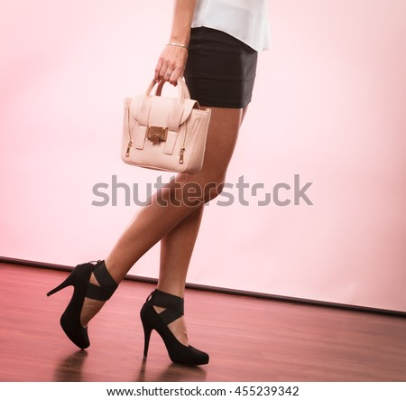 Elegant outfit. Female fashion. Girl fashionable clothes high heels shoes short skirt holding bag handbag.