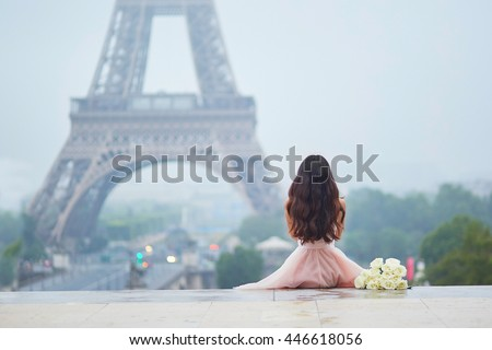 Elegant Parisian woman in pink tutu dress with white roses sitting near the Eiffel tower at Trocadero view point in Paris, France, back view - stock photo