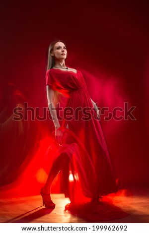 Elegant passionate young woman standing in a long red dress