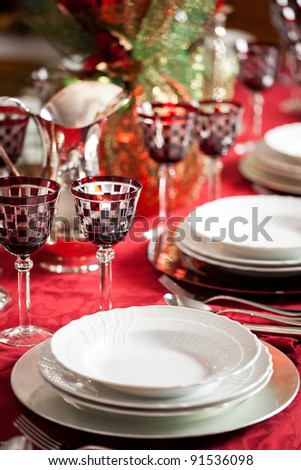Elegant place setting with white dishes over a red table cloth plus goblet and decorations - stock photo