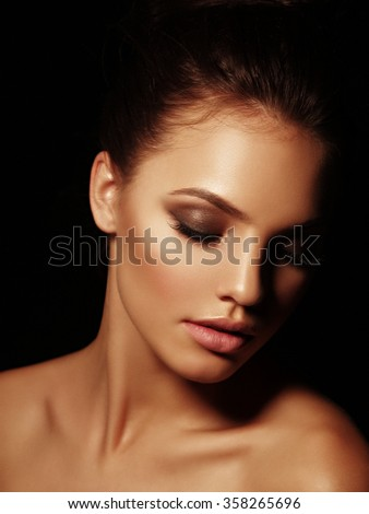 Elegant portrait of a sexy appealing naked brunette with full lips and closed eyes on the black background