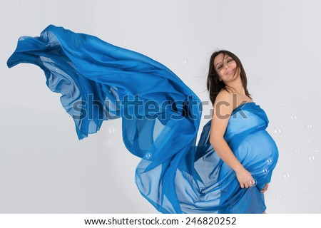 Elegant pregnant mom in wavy blue dress posing in proud of her pregnancy - stock photo