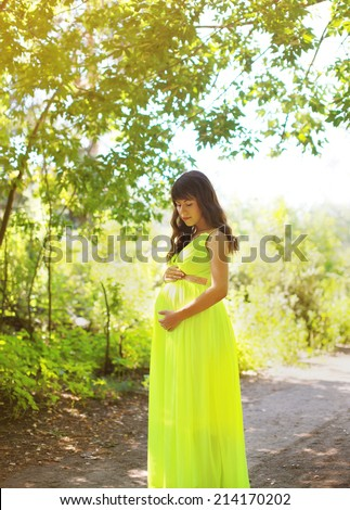 Elegant pregnant woman in dress outdoors summer - stock photo