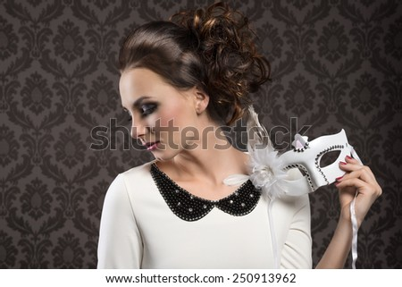 elegant pretty woman with hair style in white dress and carnival mask looking down on one side - stock photo
