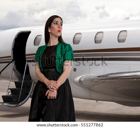 Elegant pretty young woman next to a private jet