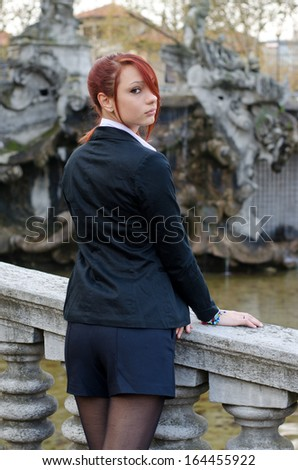 Elegant red-head girl outdoors against stone banister looking at camera over the shoulder, shot from the back