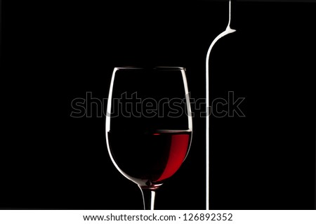Elegant red wine glass and a wine bottle in black background - stock photo