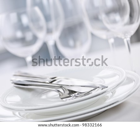 Elegant restaurant table setting with plates cutlery and stemware - stock photo