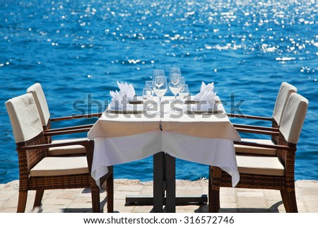 Elegant restaurant table waiting for customers by the sea; outdoor terrace in Perast, Montenegro - stock photo