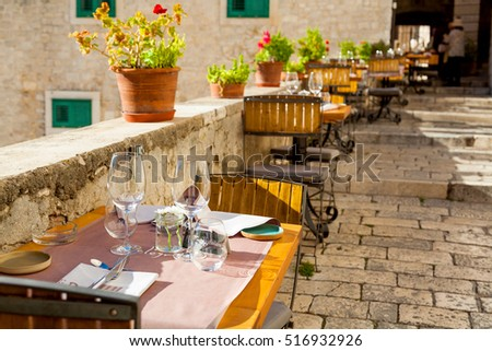 Elegant restaurant table waiting for customers; outdoor terrace in the old town of Sibenik, Croatia on 23 September 2016