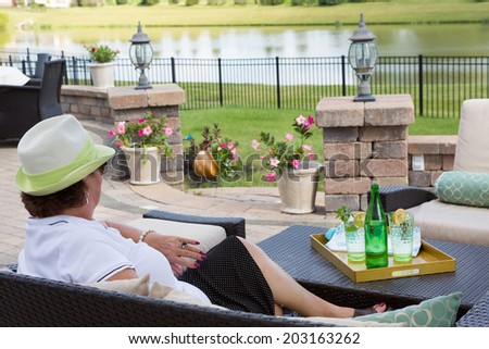 Elegant senior lady in a stylish hat relaxing on her outdoor patio with a tray of chilled bottled water garnished with lemon and mint overlooking a tranquil lake - stock photo