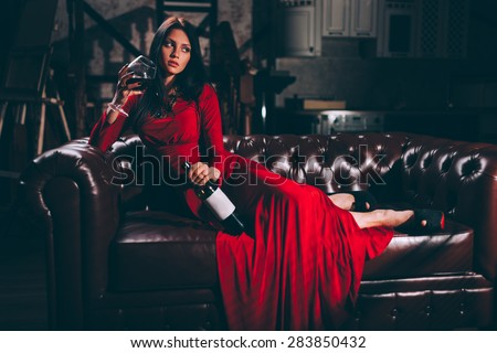 elegant sensual young brunette woman in red dress sitting on leather sofa, specially toned - stock photo
