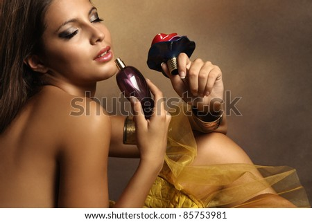 elegant sensual young woman holding perfume, golden tones, small amount of grain added - stock photo