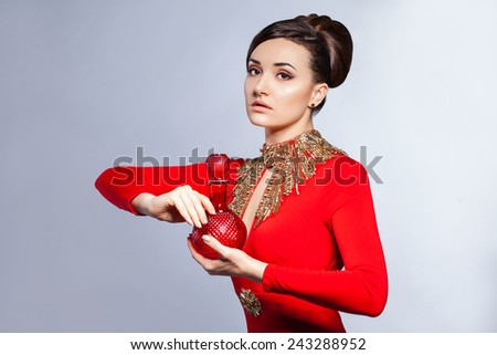 Elegant sensual young woman wearing red dress with perfume bottle - stock photo