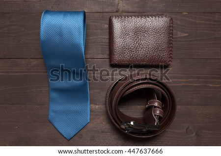 Elegant set: blue tie, brown leather belt, brown wallet, on the wooden background. - stock photo
