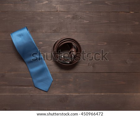 Elegant set: blue tie, brown leather belt, on the wooden background. - stock photo