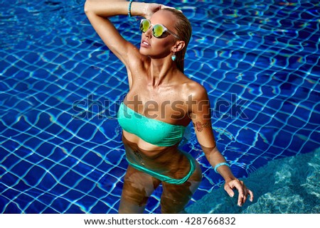 Elegant sexy woman in bikini posing in swimming pool - stock photo