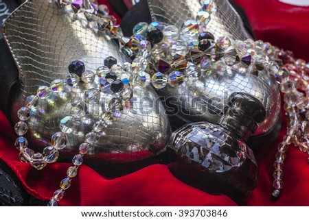 Elegant silver boots with reptile print, colored beads and black faceted bottle of perfume on red chiffon background - stock photo