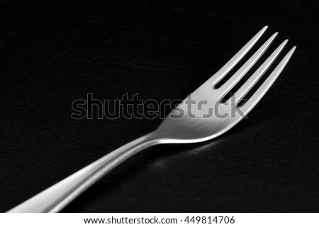 Elegant silver fork from 70s, on black background.