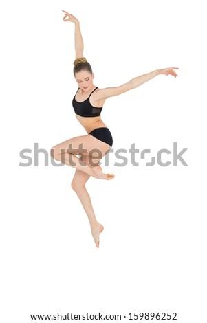 Elegant slim ballet dancer jumping in the air on white background - stock photo