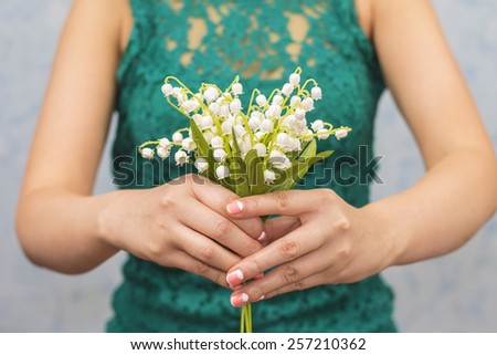 Elegant slim girl holds out lilies of valley, on blue background - stock photo