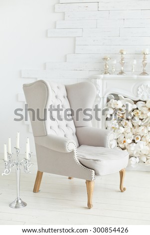 Elegant soft arm-chair near a fireplace. Luxury interior in white colors - stock photo
