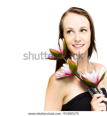 Elegant sophisticated woman in a black strapless dress and glittering necklace holding three exotic flowers over her shoulder looks back up into the frame - stock photo