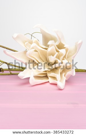 Elegant spring flower, fake gardenia on rustic wooden table. For wedding background image. - stock photo