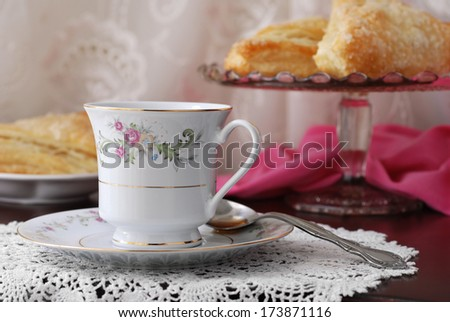Elegant still life of beautiful vintage teacup and saucer with sweet pastries on pedestal plate in background. Closeup with shallow dof. - stock photo