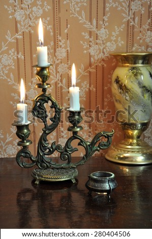 Elegant still life with ornate bronze candelabra and antique goblet on an old wallpaper background - stock photo