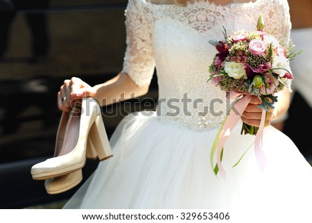 Elegant stylish bride in white vintage wedding dress shoes and bouquet in hands - stock photo