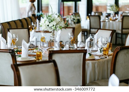 Elegant stylish decorated wedding reception tables with glasses and flowers in vase
