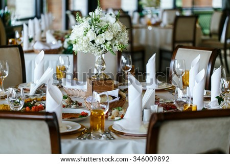 Elegant stylish decorated wedding reception tables with glasses and flowers in vase - stock photo
