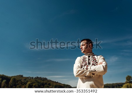 elegant stylish groom posing near a sunny lake, concept of happiness