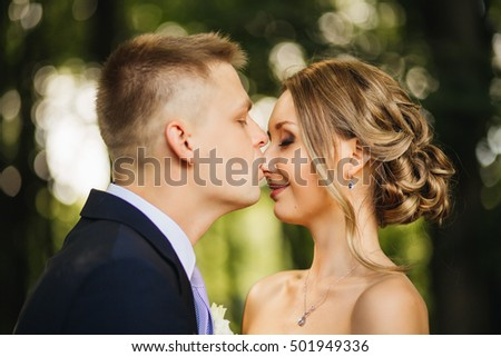 elegant stylish groom with his happy gorgeous blond bride on the background of trees
