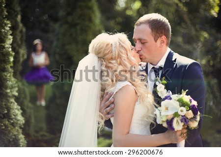 elegant stylish groom with his happy gorgeous blonde bride on the background of trees in the park