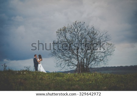 elegant stylish happy brunette bride and gorgeous groom at the sunset on the background of fall mountains