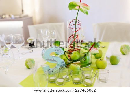 Elegant table set in white and green with apples for wedding or event party in a castle - stock photo