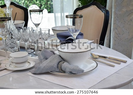 elegant table set on marble dining table in vintage style dining room interior - stock photo