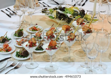 Elegant table setting in restaurant. Closeup of the luxurious dishes on a table. - stock photo