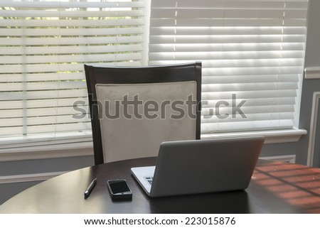 Elegant table with a laptop and cellphone - stock photo