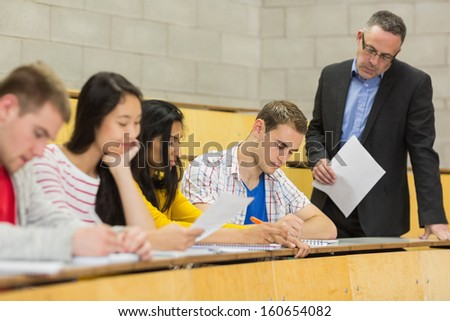Elegant teacher with students writing notes at the college lecture hall